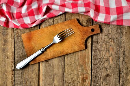 Fork on wooden cutting board and a red checkered tablecloth top frame on wooden table background Imagens - 125369895