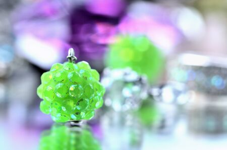 Green earring jewelery - reflection effect - colored backgrounds Imagens - 125369898