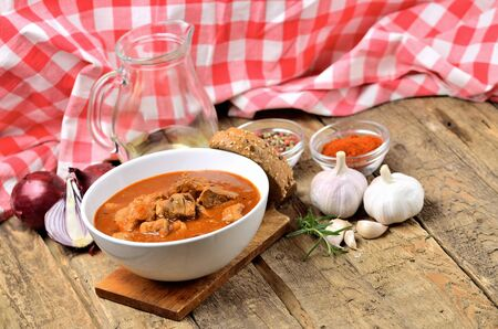 Pork goulash with pieces of meat in a bowl, garlic, pepper, onion, jug with oil and red checkered tablecloth in the background