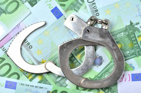 View from above of police handcuffs on euro banknotes - finance and criminality concept Imagens