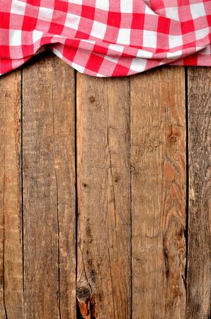 Red checkered tablecloth top frame on vintage wooden table background - view from above - vertical photo