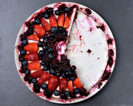 Half eaten delicious cake with fresh strawberries, blueberries, cherry jam sauce and mint leaves on slate slab. Top view.