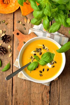 Bowl of cream pumpkin soup with fresh basil, pumpkin seed, knife and laddle on rustic wooden table. Top view. Vertical photo.