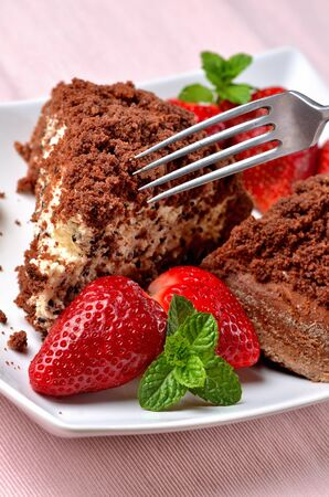 Homemade mole hole cake with whipped cream, banana, strawberries and fresh mint leaves on white decorative shaped plate. Close-up with fork. Stock Photo