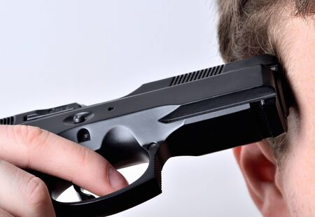 Pistol at the head - a man committing suicide by handgun- close-up detail Imagens