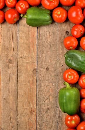 Fresh tomato and pepper on wooden background. Top view with copyspace. Vertical photo.