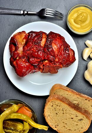 Roasted smoked pork knuckle with mustard, garlic, pickles and goat horns pepper vegetable on slate slab. Top view.