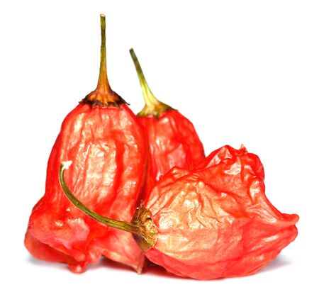 Close-up of heap of capsicum Baccatum Chilli also known as Christmas bell isolated on white background