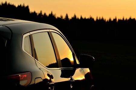 Part of modern car vehicle in nature at sunset.