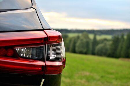 Rear brake lights of modern black SUV crossover car vehicle in nature.