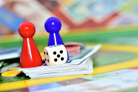 Close-up of blue, red, yellow play figures and dice on the board game. Imagens