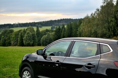 Modern black SUV crossover car vehicle in nature at sunset.