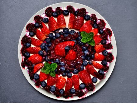Delicious cake fresh strawberries, blueberries, cherry jam and mint leaves on slate slab. Top view. Imagens