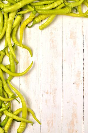 Goat horn hot green pepper chilli frame on rustic wooden white background. Top view. Copy space. Vertical photo.