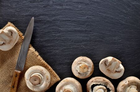 Edible half pieced mushrooms - champignons and rustic knife on vintage slate slab. Copyspace. View from above. Imagens