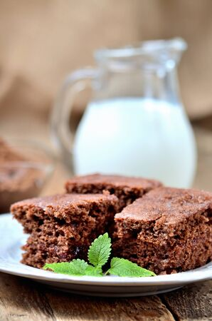 Gingerbread cakes with leaves of mint. Jug of milk in background. Imagens