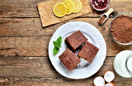 Traditional Czech gingerbread cakes, dried pieces of lemon, cacao powder, milk and raspberry jam on white plate. View from above. Imagens