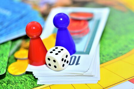 Dice, blue, red figures, chips and game money on the board. Imagens