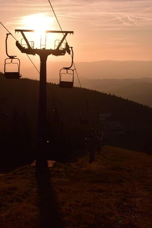 Ski chair lift in the mountains at pink sunrise. Vertical photo. 스톡 콘텐츠