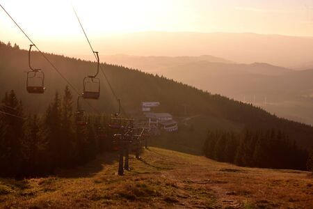Ski chair lift in the mountains at red sunset 스톡 콘텐츠