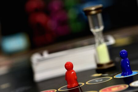 Hourglass and red, blue play figure on board games field. Archivio Fotografico - 150116917