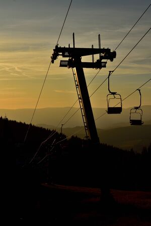 Ski chair lift in the mountains at orange sunrise. Vertical photo.
