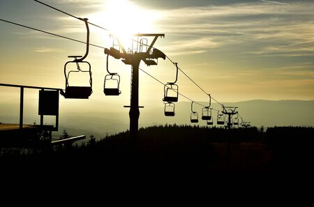 Ski chair lift in the mountains at sunset