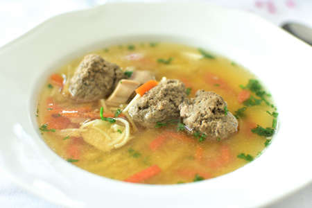 Plate full of typical Czech chicken broth with liver dumplings. Wedding soup close-up.