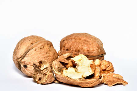 Close-up of crushed walnuts with nutshell isolated on white background