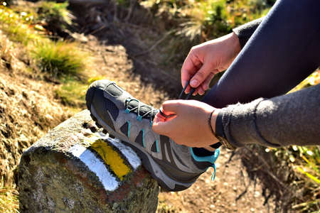 Hiker tying her trekking shoes on a hiking stone marking the tourist route