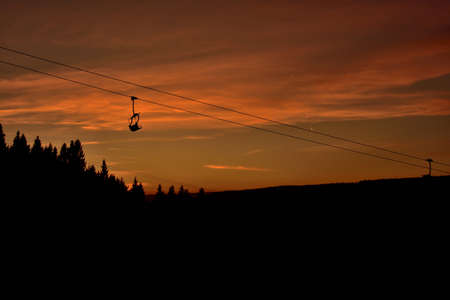 Ski chair lift in the mountains at red sunset 免版税图像