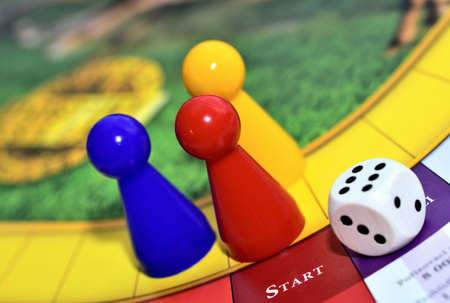 Blue, red, yellow play figures and dice on the board game 免版税图像