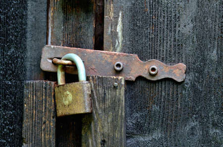 Old historical latch on wooden door and padlock. 免版税图像