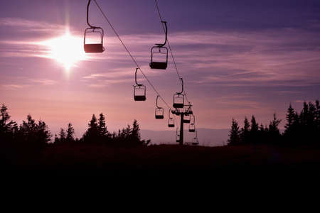 Ski chair lift in the mountains at pink sunrise