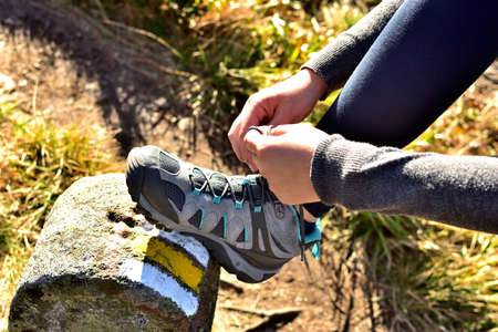 Close-up of hiker tying her trekking shoes on a hiking stone marking the tourist route