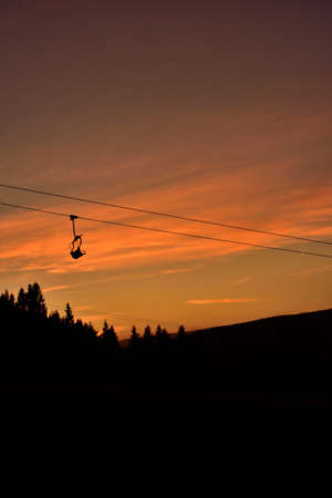 Ski chair lift in the mountains at red sunset. Vertical photo. 免版税图像