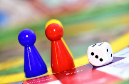 Close-up of blue, red, yellow play figures and dice on the board game. 免版税图像