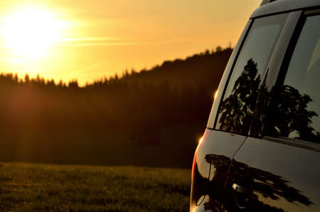 Part of modern car vehicle in nature at sunset. Forest mountain and sun in background.
