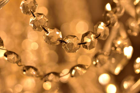 Crystal ornaments on antique chandelier. Warm white color balance. Vertical photo.