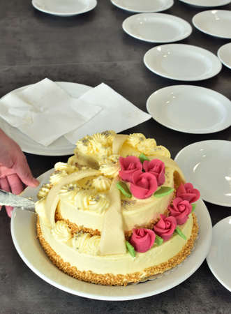 Slicing a beautifully decorated wedding cake covered with marzipan ornaments Vertical photo.