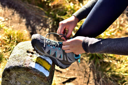 Hiker woman tying her trekking shoes on a hiking stone marking the tourist route 免版税图像