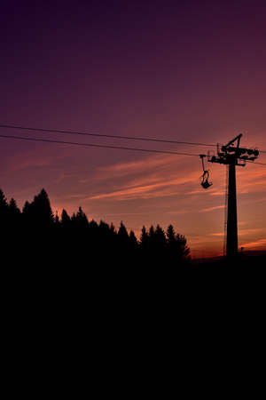 Ski chair lift in the mountains at beautiful sunset. Vertical photo.