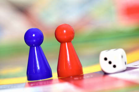 Close-up of blue, red play figures and dice on the board game.