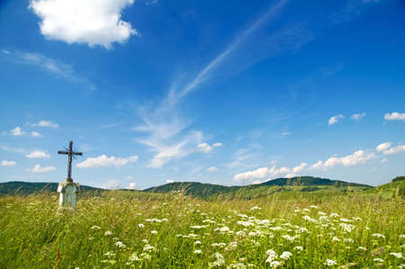 wayside: Poland, Bieszczady, Bystre. Old wayside cross on the meadow. Stock Photo
