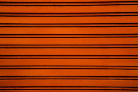 lineas horizontales: Rodillo de acero naranja Puerta del obturador fondo garaje con líneas horizontales Foto de archivo