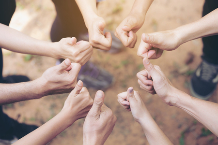 Team Work Concept : Group of Diverse Hands Together Thump up of young people in the nature.