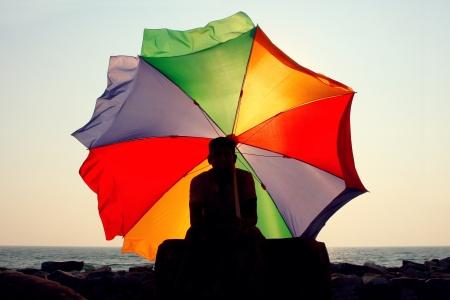 varkala: A silhouette of a man with a big rainbow umbrella