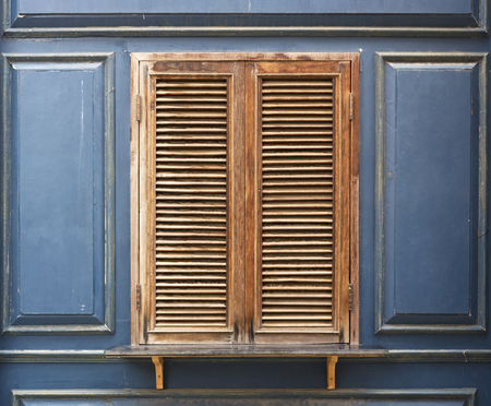 window shade: Old wooden window and blue wall. Stock Photo