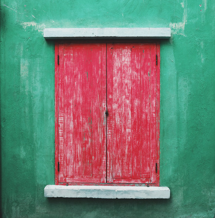 window shade: red wooden window and green wall.