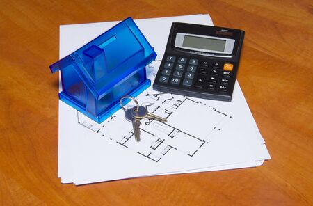 housing prices: Toy house and calculator on table